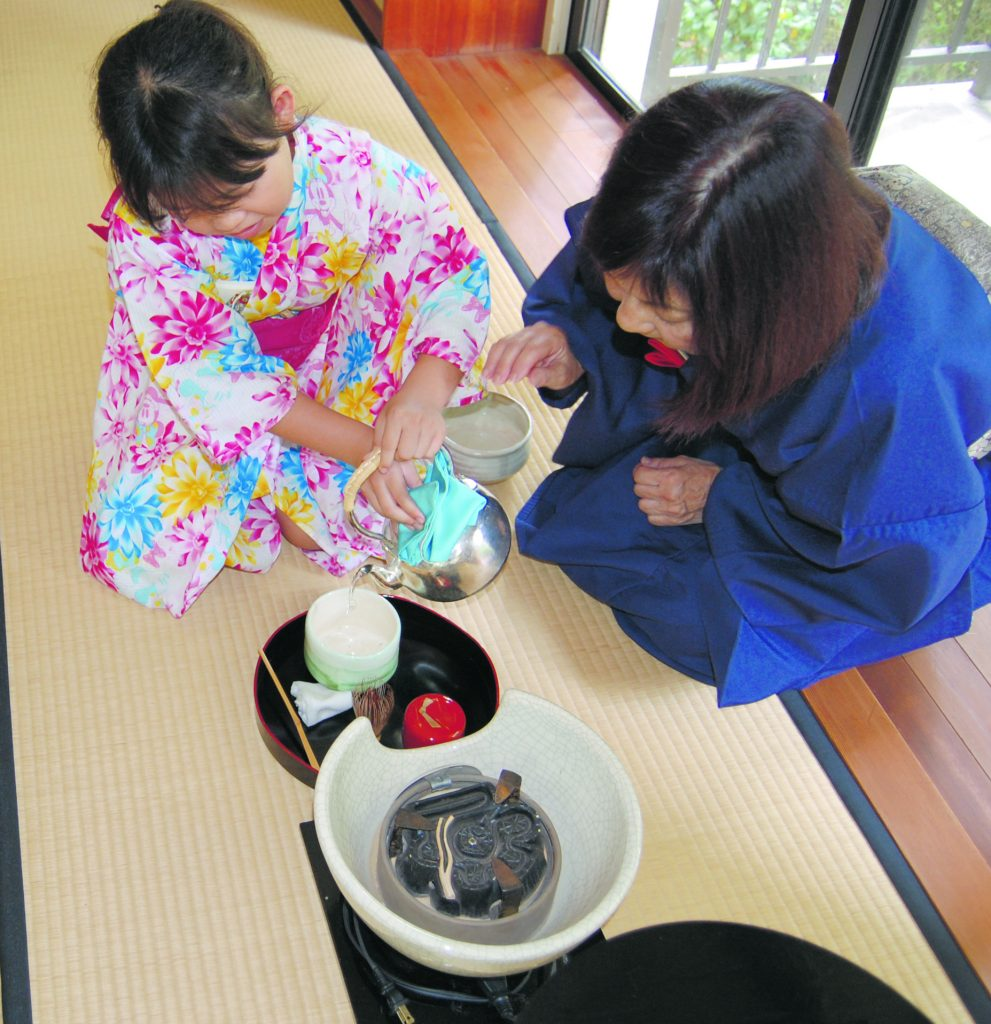 Marilyn Naka-Sensei guides Jamelyn Tomori as she pours water for tea into the tea bowl for her guest.