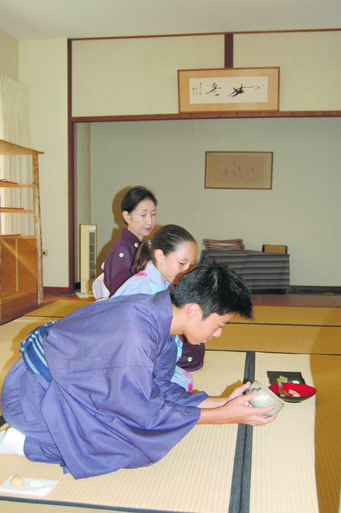 Kenjiro Otake admires the tea bowl after drinking the tea. Next to him are Ai vanDeventer and Misako Kurokawa-Sensei.