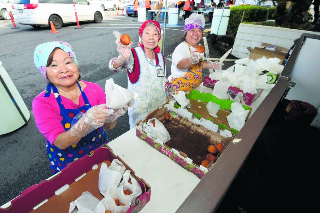 Sally Kageyama, Janet Ito and Zina Nagamine show off the fresh andagi for sale.