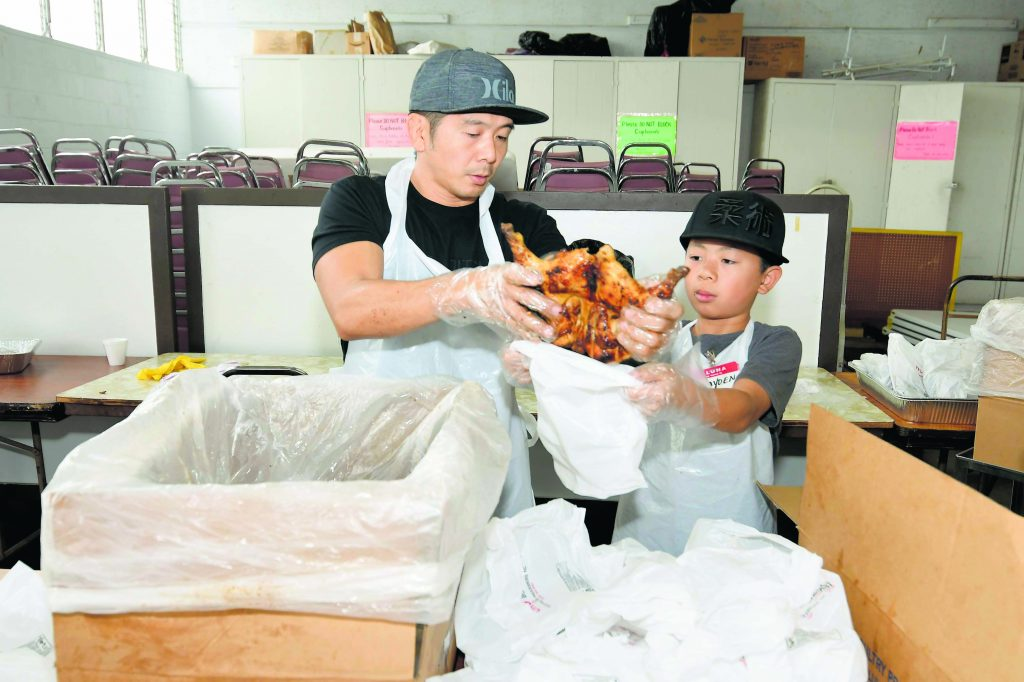 Inside the social hall, young Braden Nakamura helps his dad, Brad, pack the barbecue chicken in plastic bags.