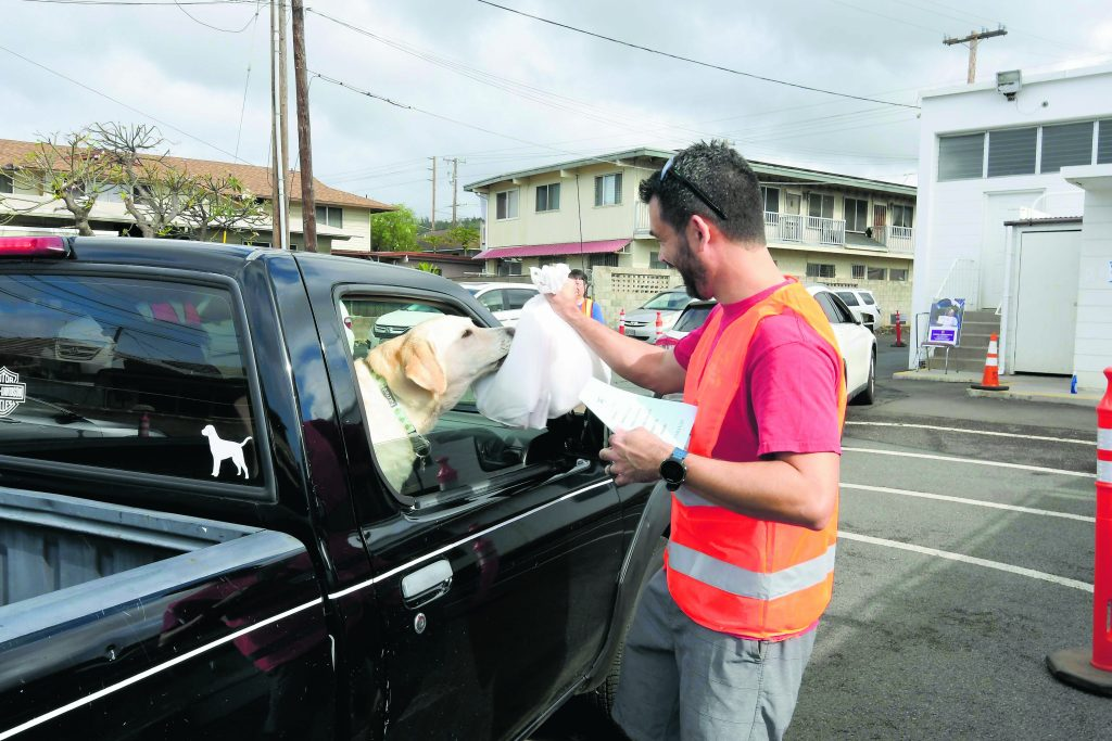 There were satisfied customers of all varieties. Even this yellow Labrador retriever was pleased with the aromas of the chicken and andagi coming from the bag that volunteer David Jones passed to the driver.