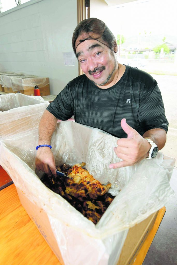 Volunteer Geno Oshiro, who is by day a school cafeteria manager, flashes a shaka while checking the temperature of the cooked chicken for safety reasons.