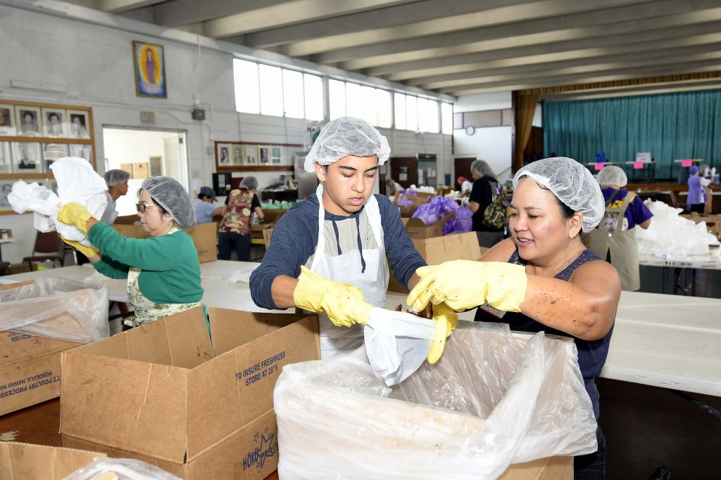 Volunteers Kai Fraser and his mother, Dawn, help bag the hot chicken.