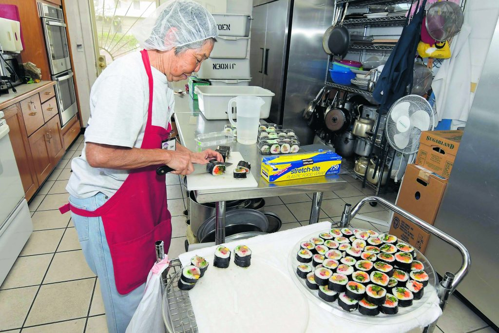 In the kitchen of Jikoen's social hall, Jean Yamashiro slices maki sushi, both tuna and veggie varieties, for volunteers to enjoy for lunch after their hard work.
