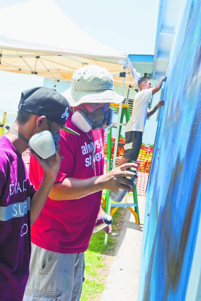 Trysen 'TK' Kaneshige working on a mural