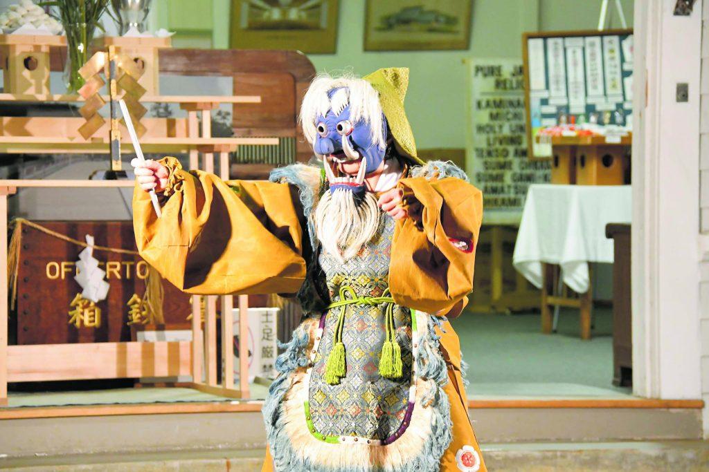 "Pauline Kawamata performs the masked dance entitled ""Rakuson,"" which means ""crouching."""