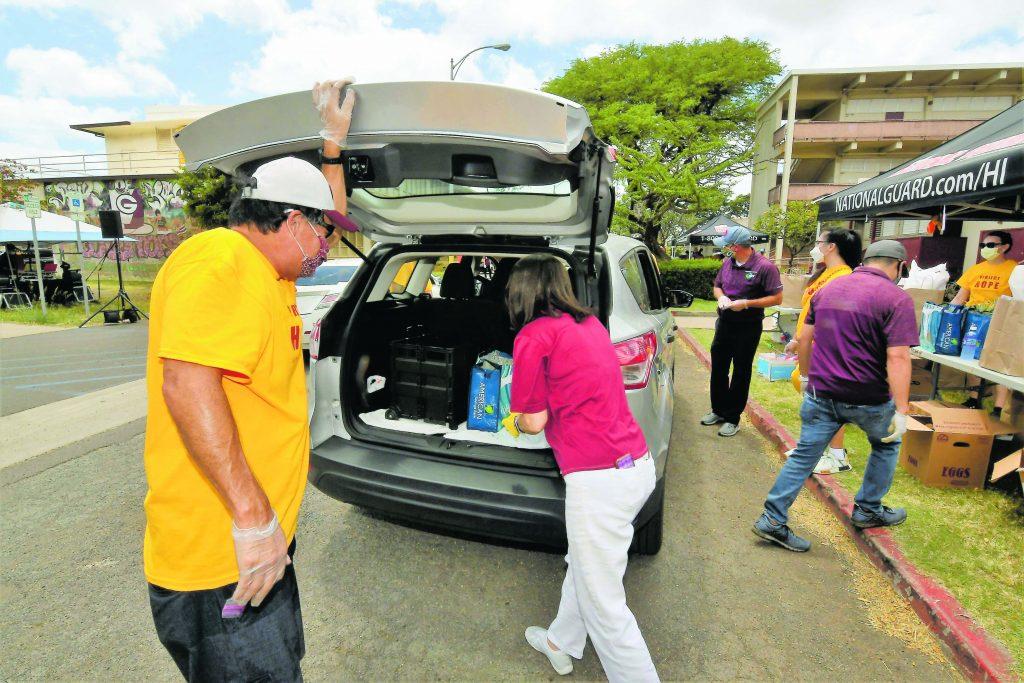 Farrington High School staff members and community volunteers load donated food.