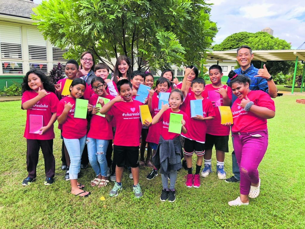 """Fourth graders from Ala Wai Elementary School show off their """"Aloha Journals"""" with their teacher, Lori Kwee (back center), Principal Michelle DeBusca (back left) and Danny Kim (far right). (Photos courtesy of Danny Kim)"""