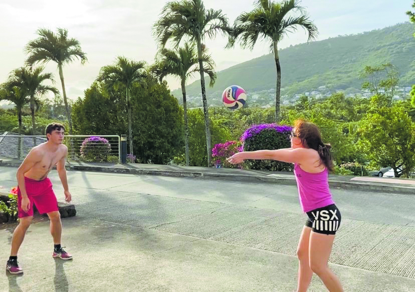 Valerie Aniya Schmidt and her son, Hunter (a high-school junior at 'Iolani School), practice volleyball drills in the driveway of their home. (Photo by Tony Schmidt)