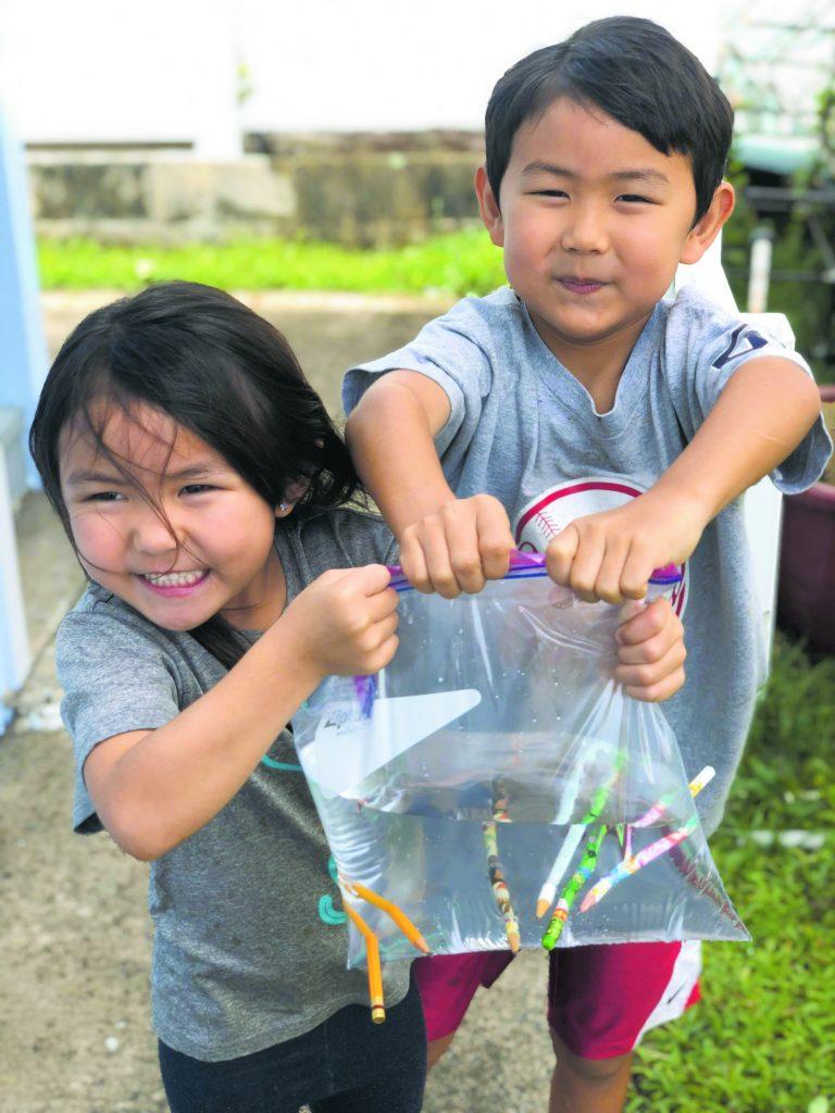 Kensi (5) and Kasen (7) Yahiku conduct a science experiment at home. (Photo by Seilee Yahiku)