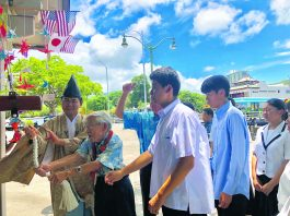 On Aug. 2, 2019, 88-year-old Hiroshima bombing survivor Lawrence Miwa, assisted by Izumo Taishakyo minister, the Rev. Jun Miyasaka, rings a replica of the Hiroshima Peace Bell. Behind him are the students from Hiroshima Minami High School.