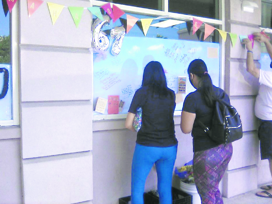 """On April 30, the official closing date, Likelike Drive Inn employees taped sky-blue posterboards to the storefront and left colorful pens for the community. Diners wrote messages, offered balloons and flowers, and even posted photo arrays of happy eaters, now memories of the past. The """"67"""" means years in business. (Photo courtesy of Kenrick Yoshida)"""