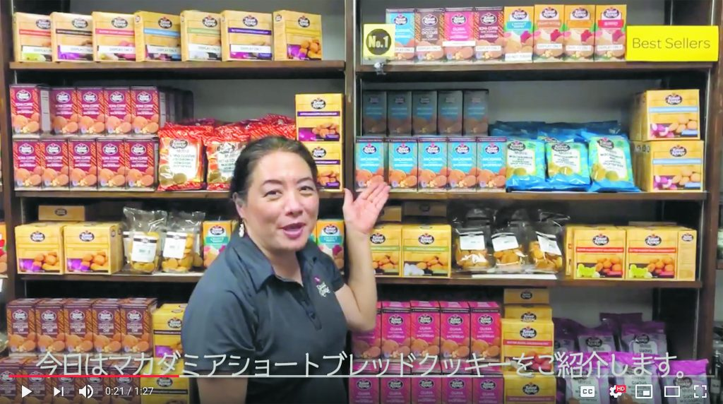 """While introducing the """"macadamia shortbread cookie"""" of her mother's Kauai Kookie Company to Japanese viewers, Ann Hashisaka also briefly talks about the history of Japanese immigrant labor in Hawai'i in this promotional clip for Natural Lawson convenience store's Hawaii Fair. (Photo courtesy of Natural Lawson's YouTube channel)"""