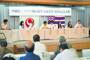 Michelle Whaley (second from the left) represents her mother, the late Jane Serikaku, who was an executive director for the Hawaii United Okinawa Association and a student-exchange coordinator for the Hawaii-Okinawa Student Exchange Program. Next to Whaley is HOSEP coordinator Tom Yamamoto (third from left). Student Michelle Nitta has the mic, speaking on behalf of Hawai'i high-school students. (Photo courtesy of Tom Yamamoto)