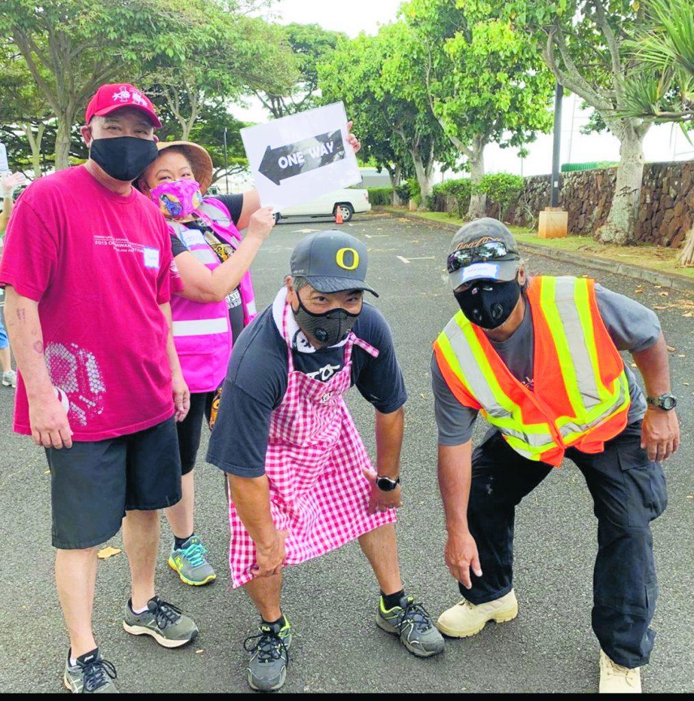 HUOA Executive Director Jon Itomura (in an apron) and volunteers direct customers to fresh andagi.