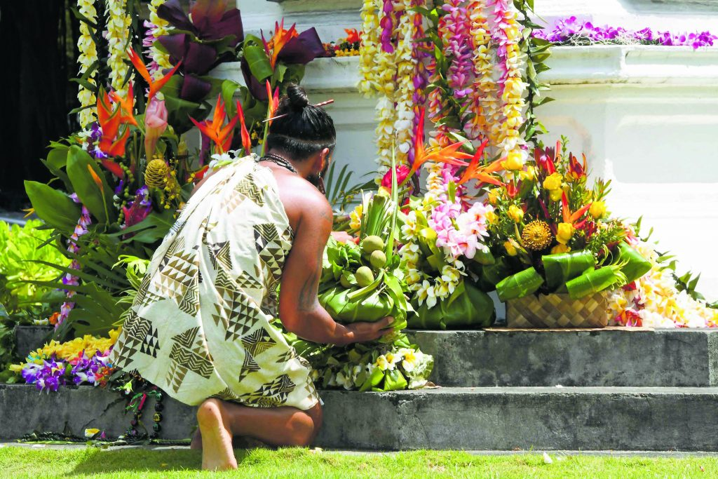 The ho'okupu is placed at the base of the King Kamehameha statue among an abundance of lei and floral arrangements.