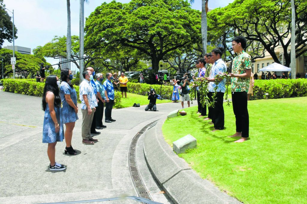Representatives of the Kamehameha Schools offer lei at the statue of King Kamehameha.